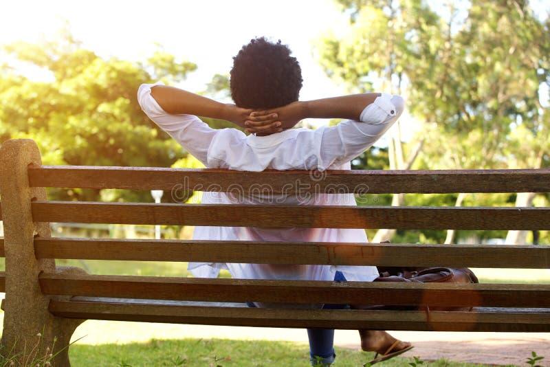 Młodej damy obsiadanie relaksujący na parkowej ławce zdjęcie royalty free