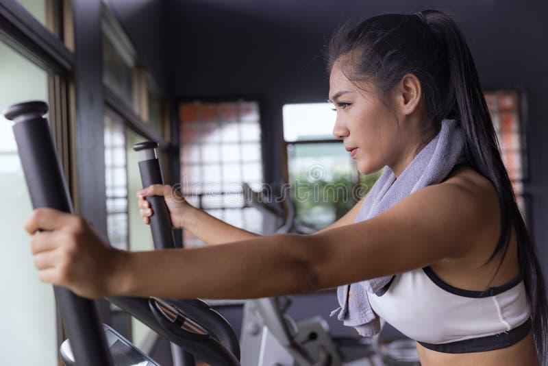 Młodej dziewczyny ćwiczenia roweru cardio trening przy sprawności fizycznej gym zdjęcie royalty free