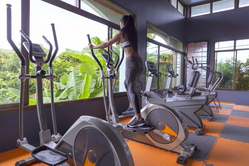Młodej dziewczyny ćwiczenia roweru cardio trening przy sprawności fizycznej gym obraz royalty free