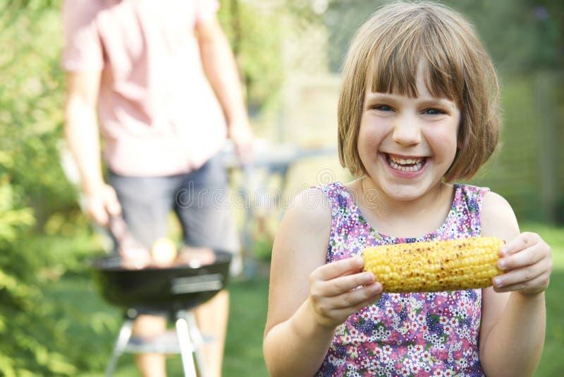 Młodej Dziewczyny łasowania Sweetcorn Przy Rodzinnym grillem obrazy royalty free
