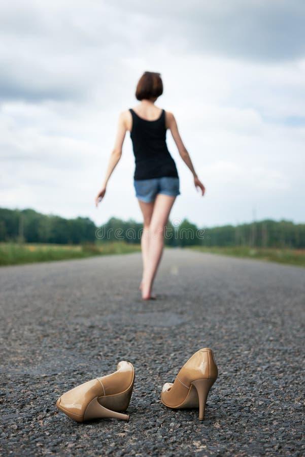 Młodej dziewczyny chodzić bosy na drodze, opuszczał jej buty na drodze i zapominał one pojęcie lato i podróż, obraz royalty free