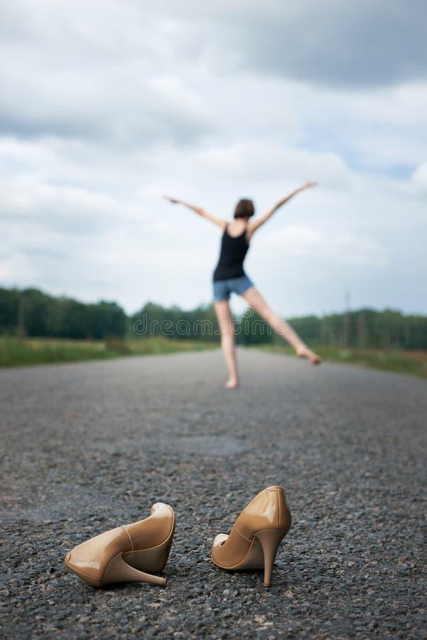 Młodej dziewczyny chodzić bosy na drodze, opuszczał jej buty na drodze i zapominał one pojęcie lato i podróż, zdjęcia stock