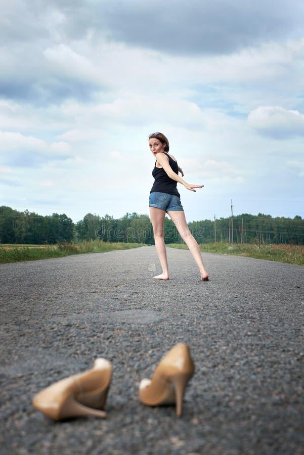 Młodej dziewczyny chodzić bosy na drodze, opuszczał jej buty na drodze i zapominał one pojęcie lato i podróż, obrazy royalty free