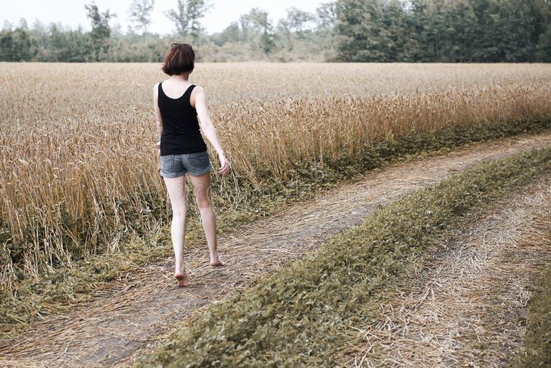 Młodej dziewczyny chodzić bosy na drodze, opuszczał jej buty na drodze i zapominał one pojęcie lato i podróż, fotografia royalty free