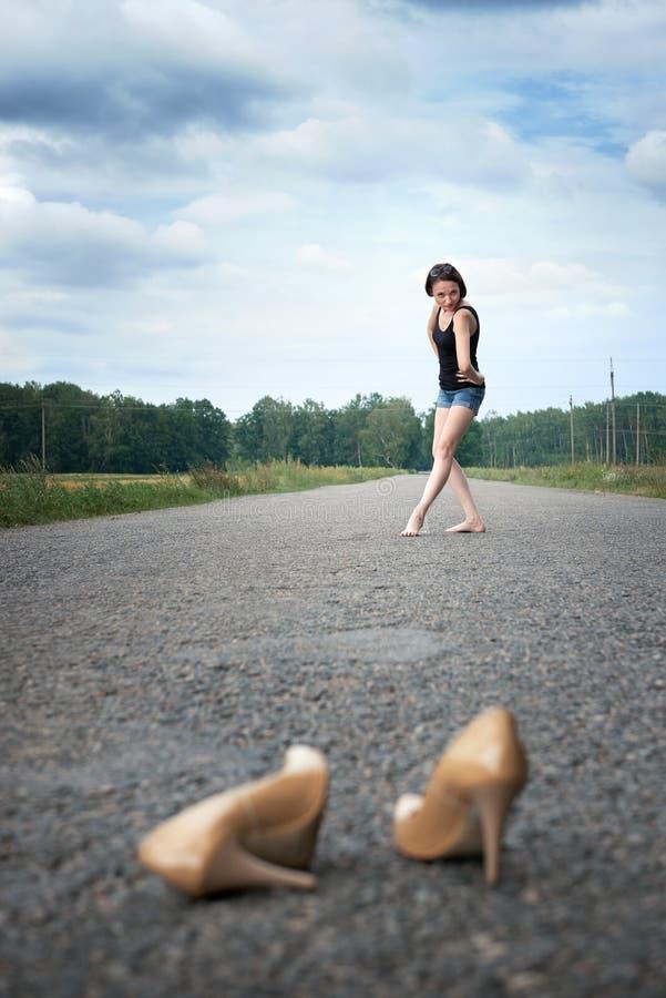 Młodej dziewczyny chodzić bosy na drodze, opuszczał jej buty na drodze i zapominał one pojęcie lato i podróż, obrazy stock