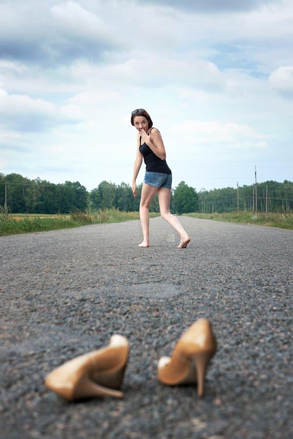 Młodej dziewczyny chodzić bosy na drodze, opuszczał jej buty na drodze i zapominał one pojęcie lato i podróż, fotografia stock