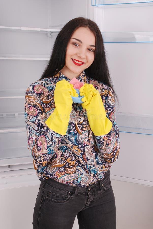 Młodej dziewczyny cleaning pusty fridge z gąbką fotografia royalty free