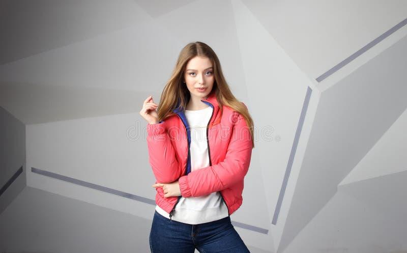 Młodej dziewczyny dziewczyna jest ubranym kurtkę z terenem dla twój logo w górę białej kobiety hoodie, obraz stock