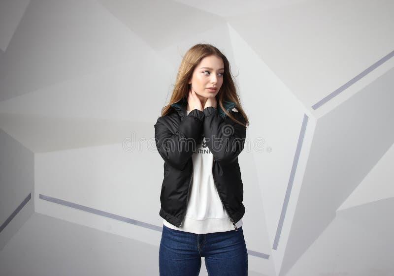 Młodej dziewczyny dziewczyna jest ubranym kurtkę z terenem dla twój logo w górę białej kobiety hoodie, fotografia royalty free