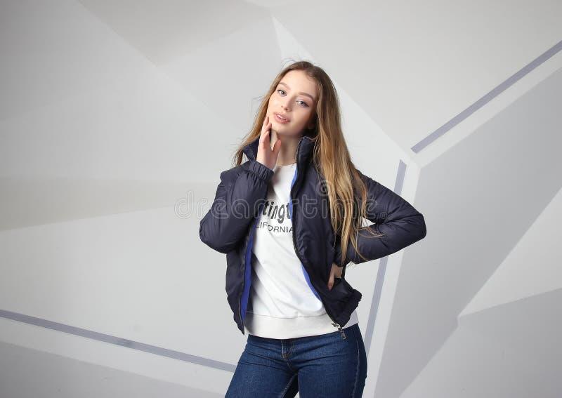 Młodej dziewczyny dziewczyna jest ubranym kurtkę z terenem dla twój logo w górę białej kobiety hoodie, zdjęcie stock
