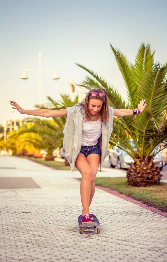 Młodej dziewczyny jazda w deskorolka outdoors obrazy royalty free