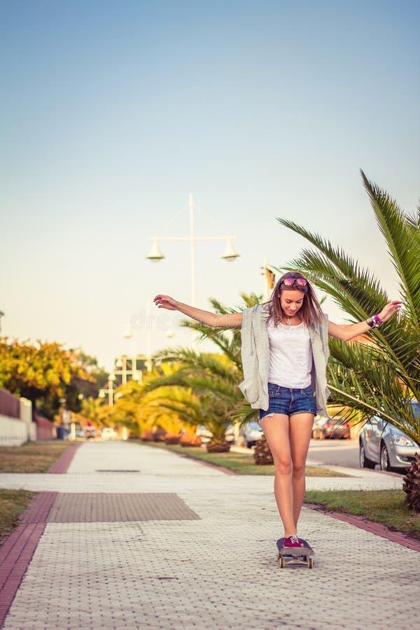 Młodej dziewczyny jazda w deskorolka outdoors dalej obrazy royalty free