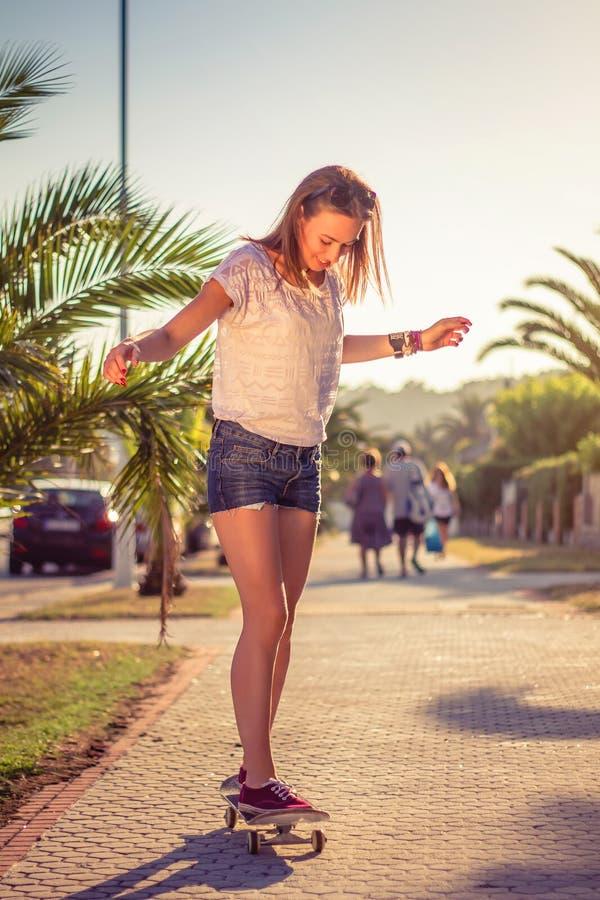 Młodej dziewczyny jazda w deskorolka outdoors dalej fotografia royalty free