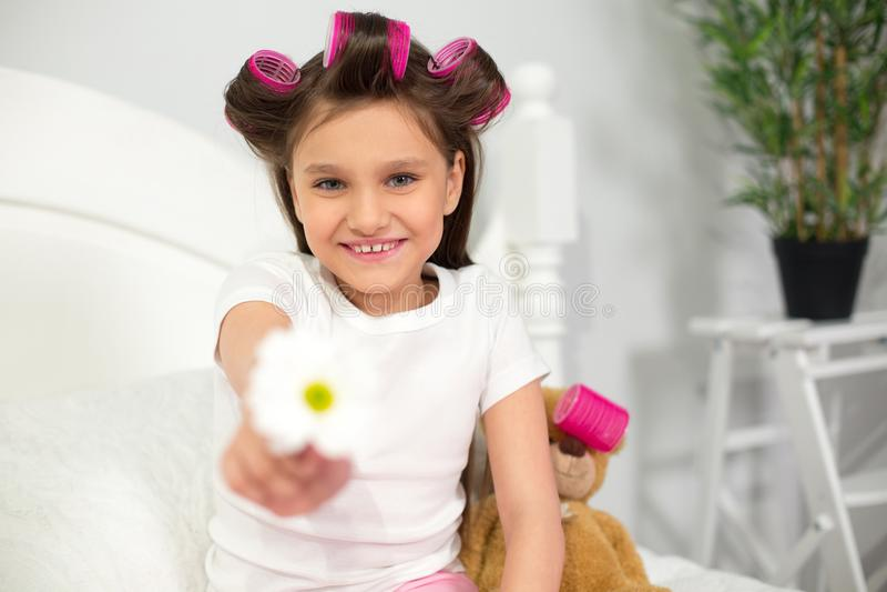 Młodej dziewczyny obsiadanie na jej łóżku z kwiatem zdjęcia stock
