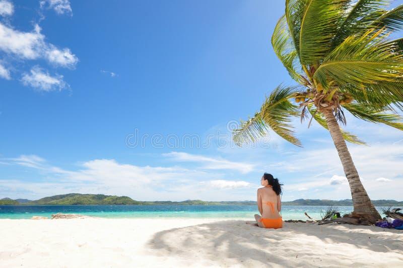Młodej dziewczyny obsiadanie na plaży pod kokosowym drzewem zdjęcia stock