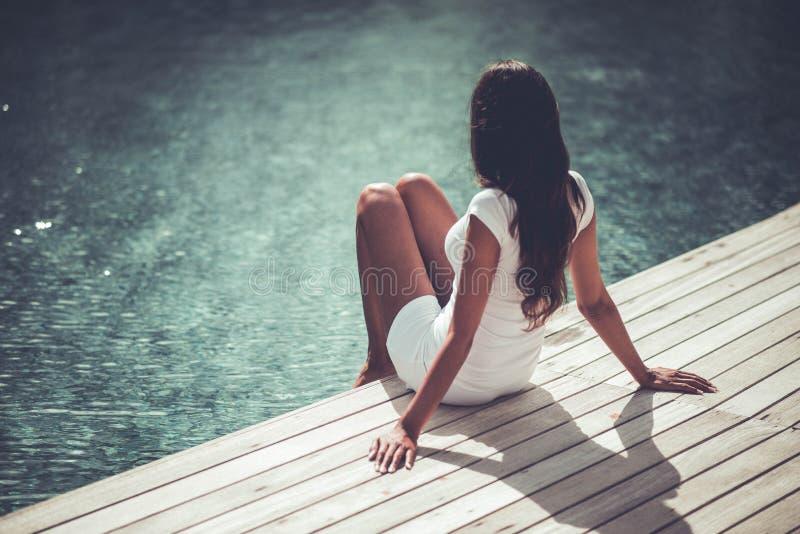 Młodej dziewczyny obsiadanie obok pływackiego basenu zdjęcia stock