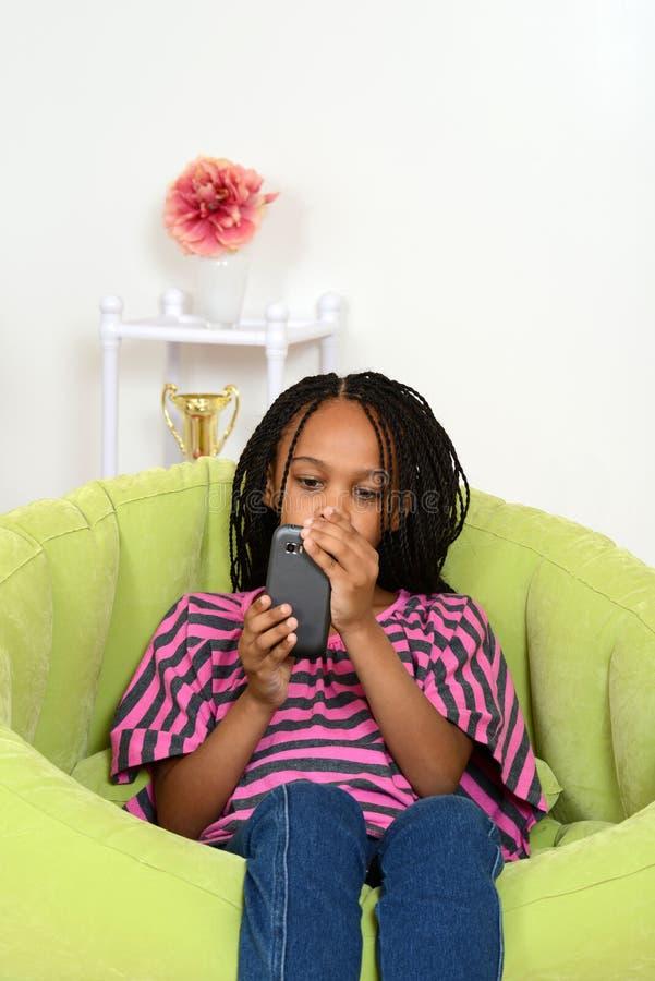 Młodej dziewczyny obsiadanie używać telefon komórkowy obrazy royalty free