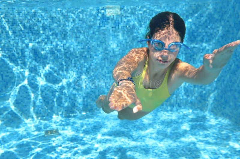 Młodej dziewczyny pływaczki dopłynięcie pod wodą w basenie i zabawę, nastolatek nurkuje wakacje, sport i sprawność fizyczną podwo obrazy royalty free