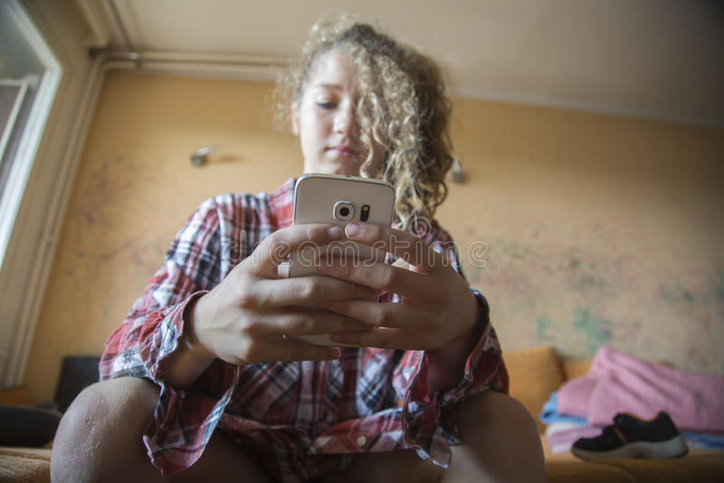 Młodej dziewczyny piękna rudzielec kobiety writing wiadomość na telefonie komórkowym Patrzeć w dół obrazy royalty free