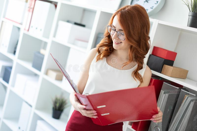 Młodej dziewczyny piękni stojaki blisko sterty w chwytach i biurze falcówka z dokumentami w jej rękach obrazy stock