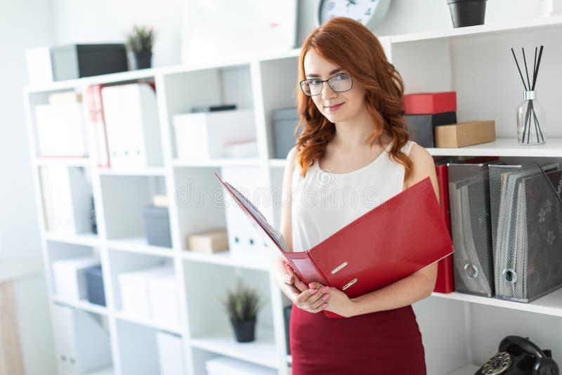 Młodej dziewczyny piękni stojaki blisko sterty w chwytach i biurze falcówka z dokumentami w jej rękach zdjęcie stock