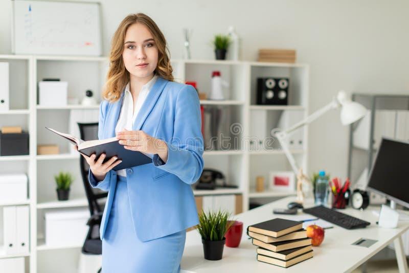 Młodej dziewczyny piękni stojaki blisko stołu w chwytach i biurze otwarta książka w ona ręki zdjęcie royalty free