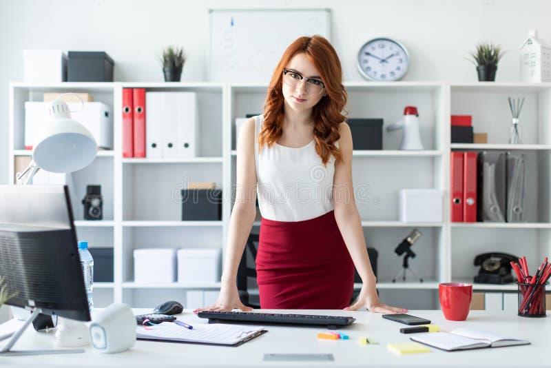 Młodej dziewczyny piękni stojaki w biurze blisko stołu, stawia jej ręki na nim obraz royalty free