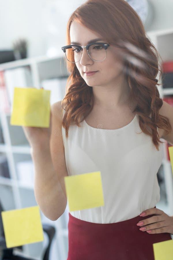 Młodej dziewczyny piękni stojaki w biurze blisko szkła na którym klajstrują majchery Dziewczyna trzyma ołówek wewnątrz obrazy royalty free