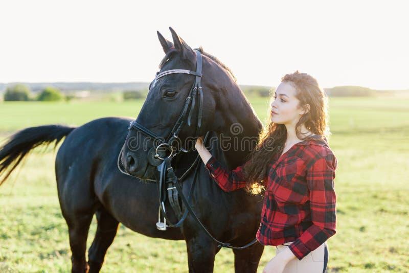 Młodej dziewczyny pozycja obok pięknego ciemnego konia obraz royalty free