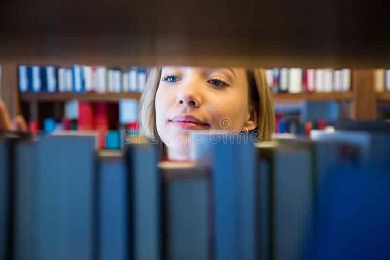 Młodej dziewczyny pozycja w tradycyjnej starej bibliotece zdjęcie stock
