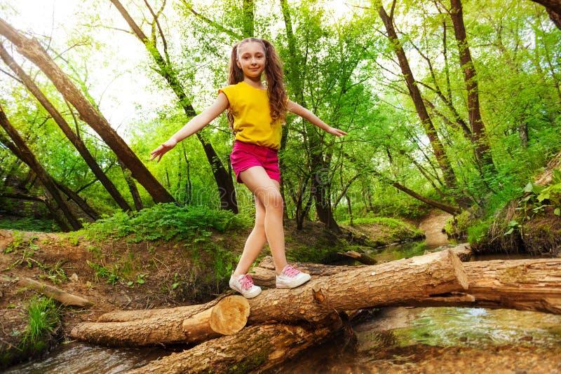 Młodej dziewczyny równoważenie na beli krzyżuje nad rzeką zdjęcia royalty free