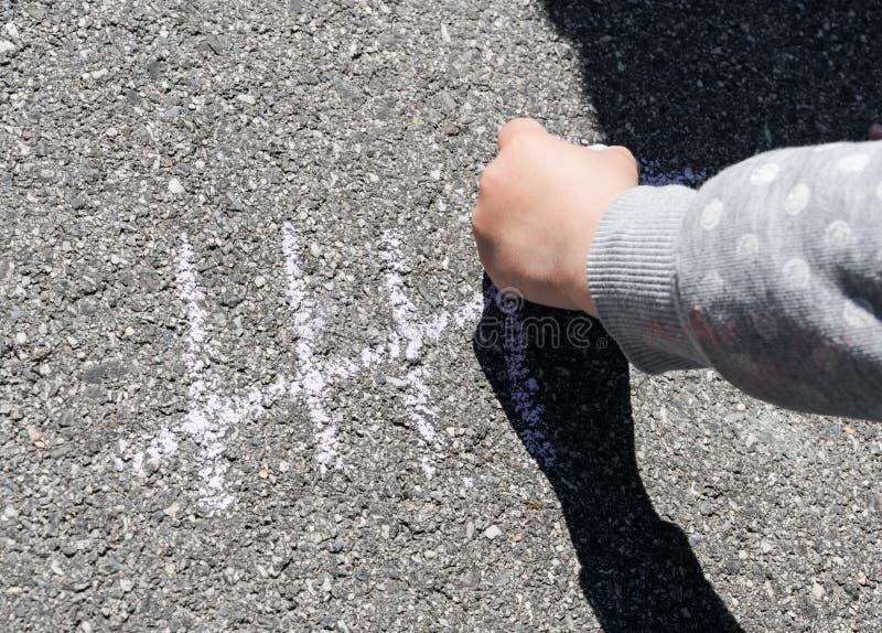 Młodej dziewczyny ręka trzyma gęstą kredę i pisze jej wieku na ulicie zdjęcie stock