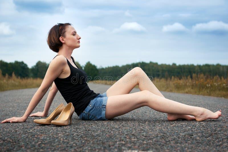 Młodej dziewczyny siedzieć bosy na drodze, opuszczał jej buty na drodze i zapominał one pojęcie lato i podróż, fotografia stock