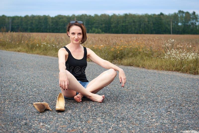 Młodej dziewczyny siedzieć bosy na drodze, opuszczał jej buty na drodze i zapominał one pojęcie lato i podróż, zdjęcie stock