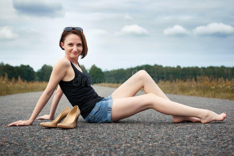 Młodej dziewczyny siedzieć bosy na drodze, opuszczał jej buty na drodze i zapominał one pojęcie lato i podróż, obraz stock