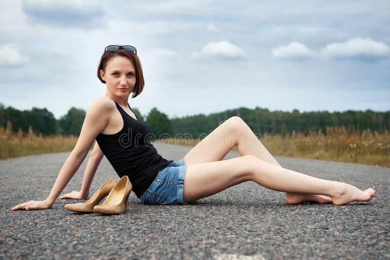 Młodej dziewczyny siedzieć bosy na drodze, opuszczał jej buty na drodze i zapominał one pojęcie lato i podróż, obrazy stock