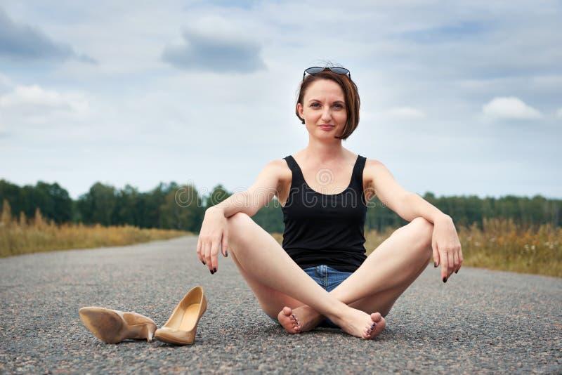 Młodej dziewczyny siedzieć bosy na drodze, opuszczał jej buty na drodze i zapominał one pojęcie lato i podróż, obraz royalty free