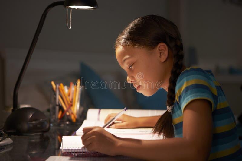 Młodej Dziewczyny studiowanie Przy biurkiem W sypialni W wieczór zdjęcie stock