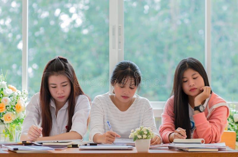 Młodej dziewczyny szkoły wyższa Azjatyckie grupy ucznie używa pastylkę, nauka obraz stock