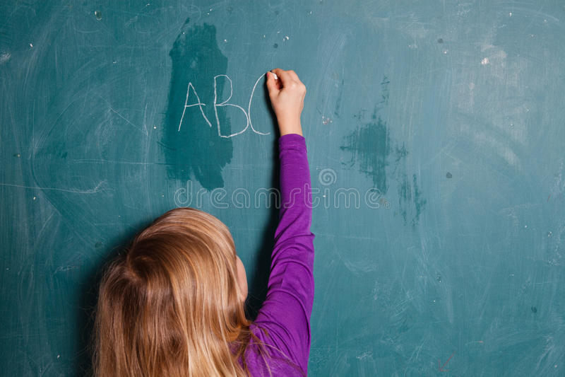 Młodej dziewczyny writing listy na chalkboard zdjęcie stock