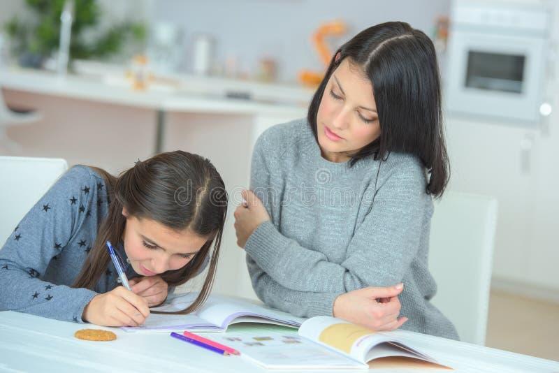 Młodej dziewczyny writing w książce z mum fotografia stock