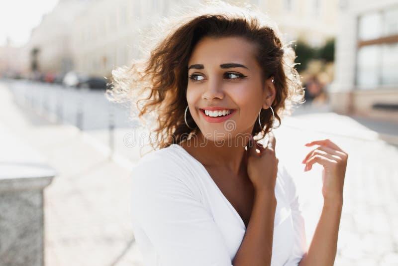 Młodej ekspresyjnej brunetki kędzierzawa kobieta z brązu dębnikiem, naturalny i robimy upwalking w dół ulicę fotografia stock