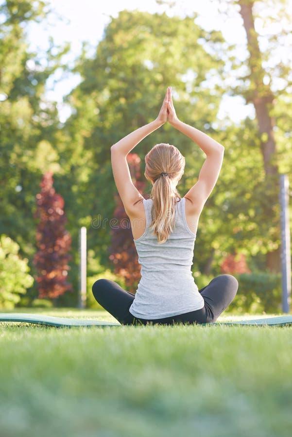 Młodej kobiety ćwiczy joga outdoors przy parkiem obraz stock