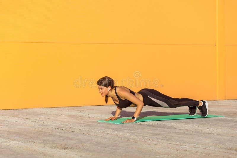 Młodej kobiety ćwiczy joga, robi cztery limbed personelu, pcha ups lub prasa ups ćwiczenie, chaturanga dandasana poza, opracowywa zdjęcia royalty free