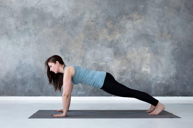 Młodej kobiety ćwiczy joga, robi Pcha ups lub prasa ups ćwiczenie, deski poza zdjęcie royalty free