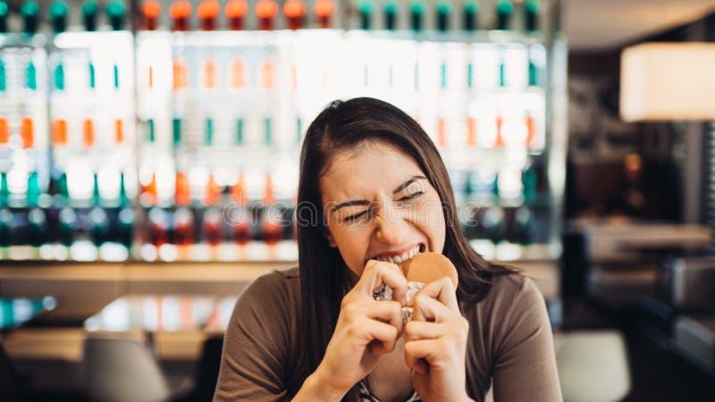 Młodej kobiety łasowania grubasa hamburger Pragnienie fast food Cieszący się winną przyjemność, je szybkie żarcie Zadowolony wyra zdjęcie stock