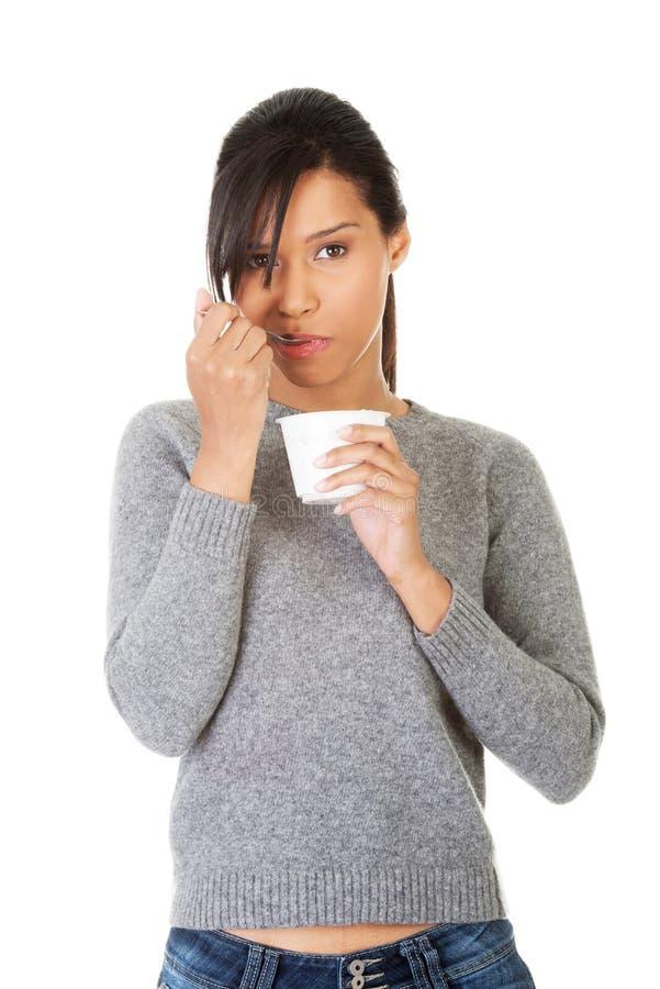 Młodej kobiety łasowania jogurt jako zdrowy śniadanie lub przekąska. zdjęcie royalty free