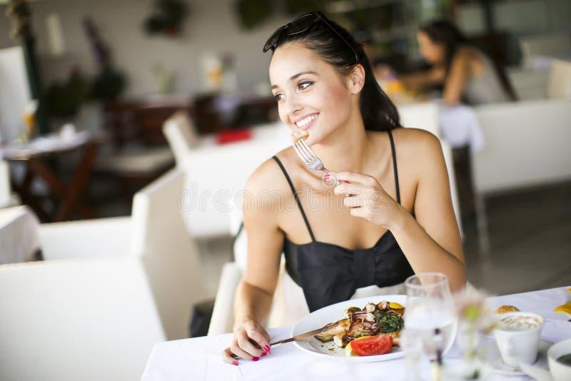 Młodej kobiety łasowanie w restauraci zdjęcie stock