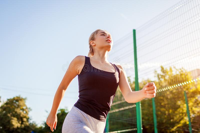 Młodej kobiety atlety bieg na sportsground w lecie zdrowe życie obrazy royalty free