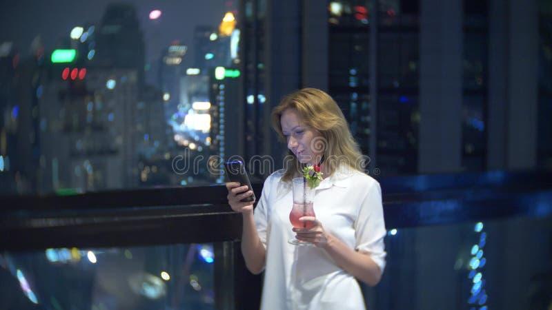 Młodej kobiety blondynka relaksuje koktajl w barze i pije z widokiem drapacz chmur przy nocą tła plamy kwiat spojrzenie lubi spoj obrazy royalty free